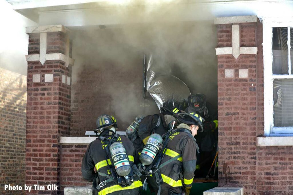 Firefighters push into the interior of a home with a handline