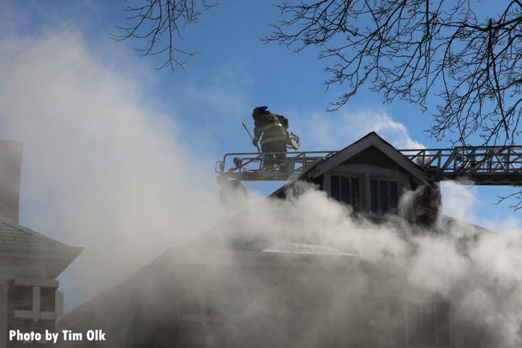 Smoke drifts up from a fire as a Chicago firefighter operates on an aerial ladder