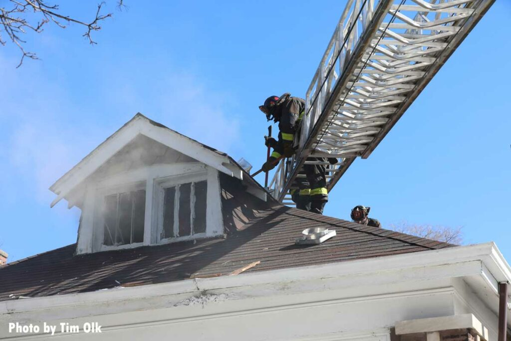 Chicago firefighters on an aerial performing roof ops