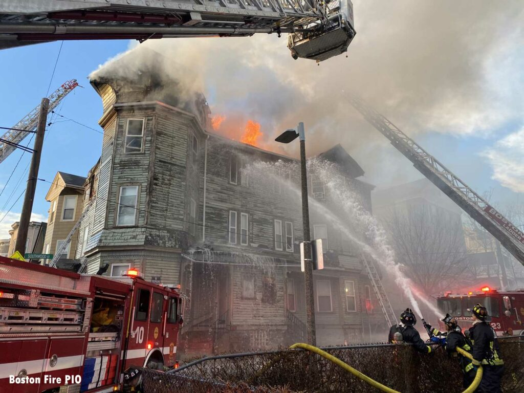 Flames shoot through the roof of the building as firefighters apply water
