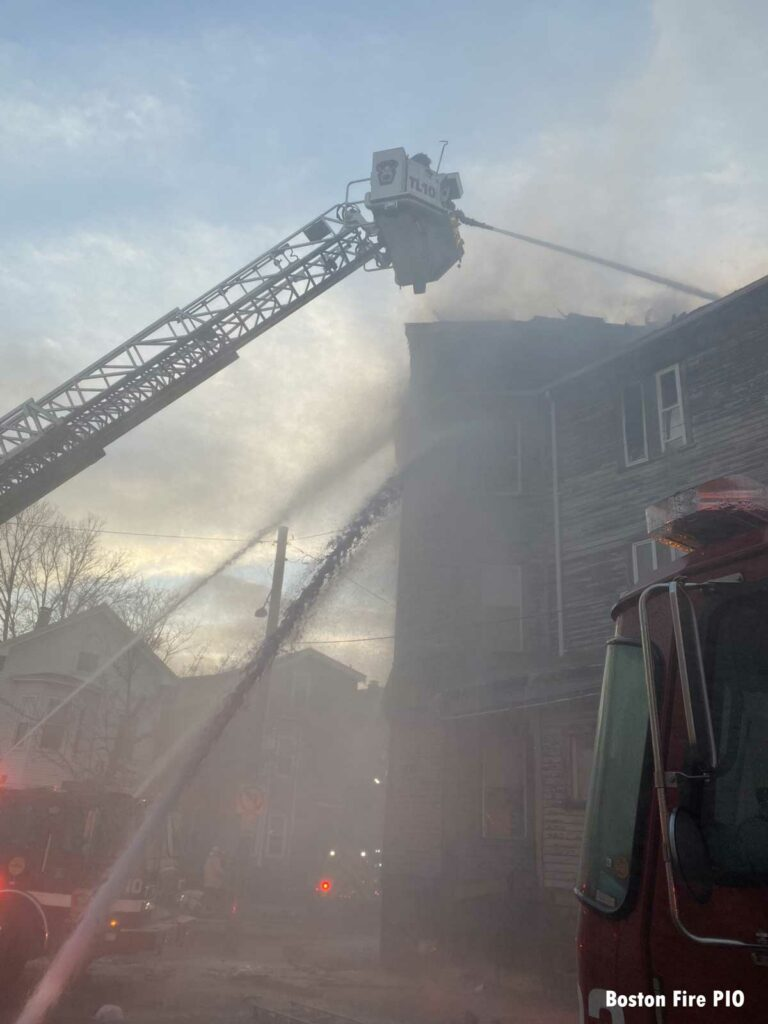 Boston tower ladder with firefighters in bucket directing stream