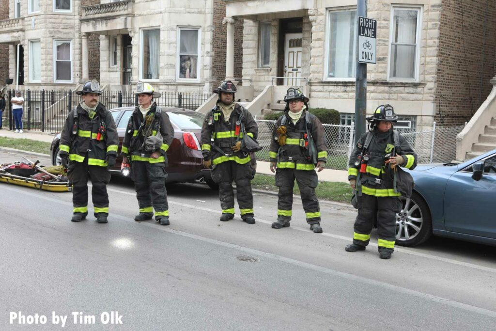 Five Chicago firefighters in full gear at the fire scene