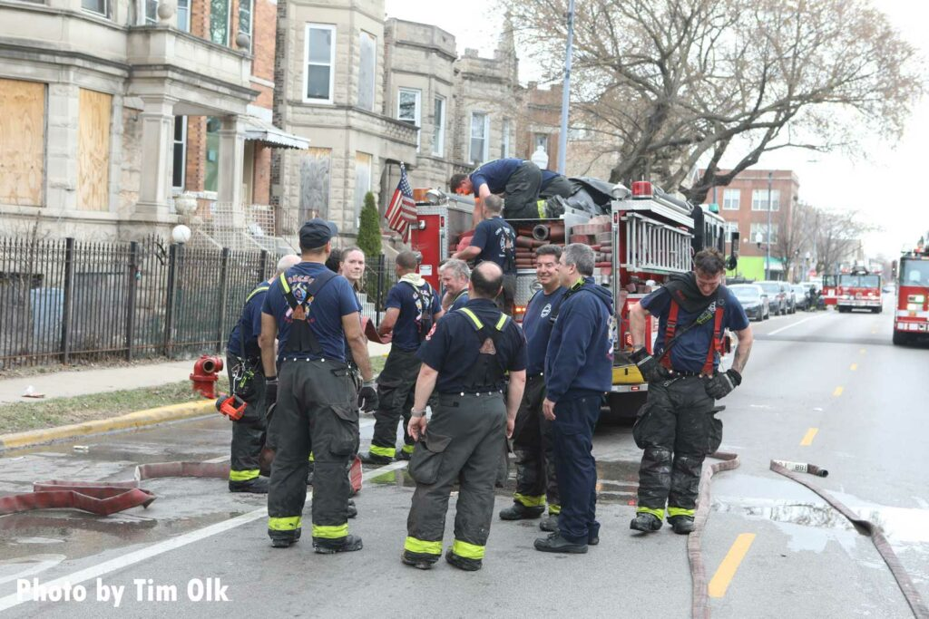 Chicago firefighters discuss the incident on the back step of an apparatus