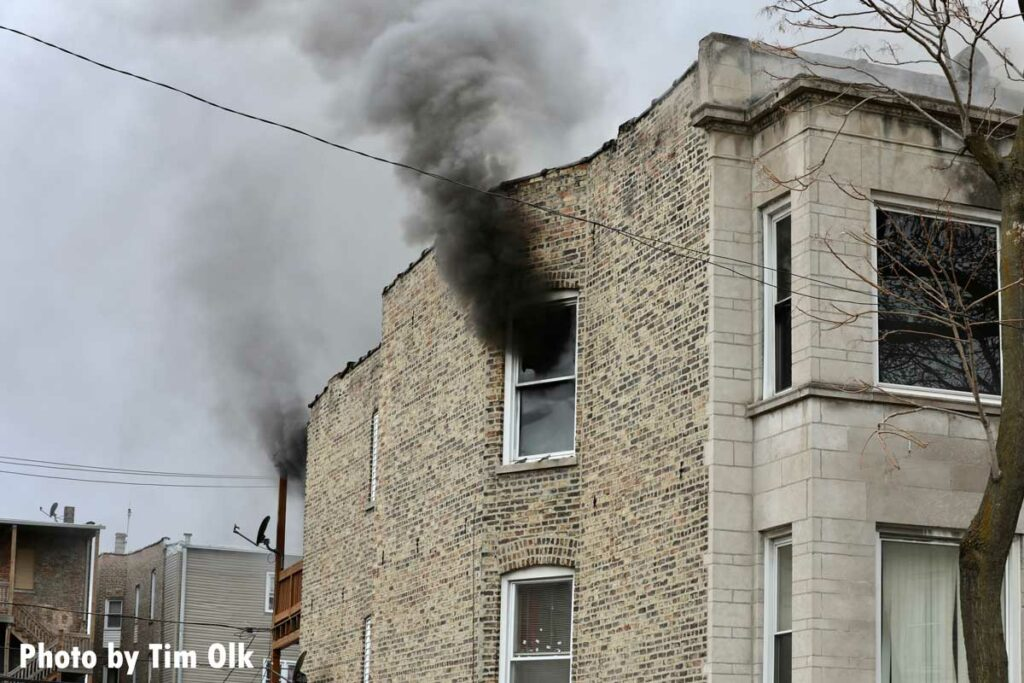Black smoke shoots from a window and the rear of the building