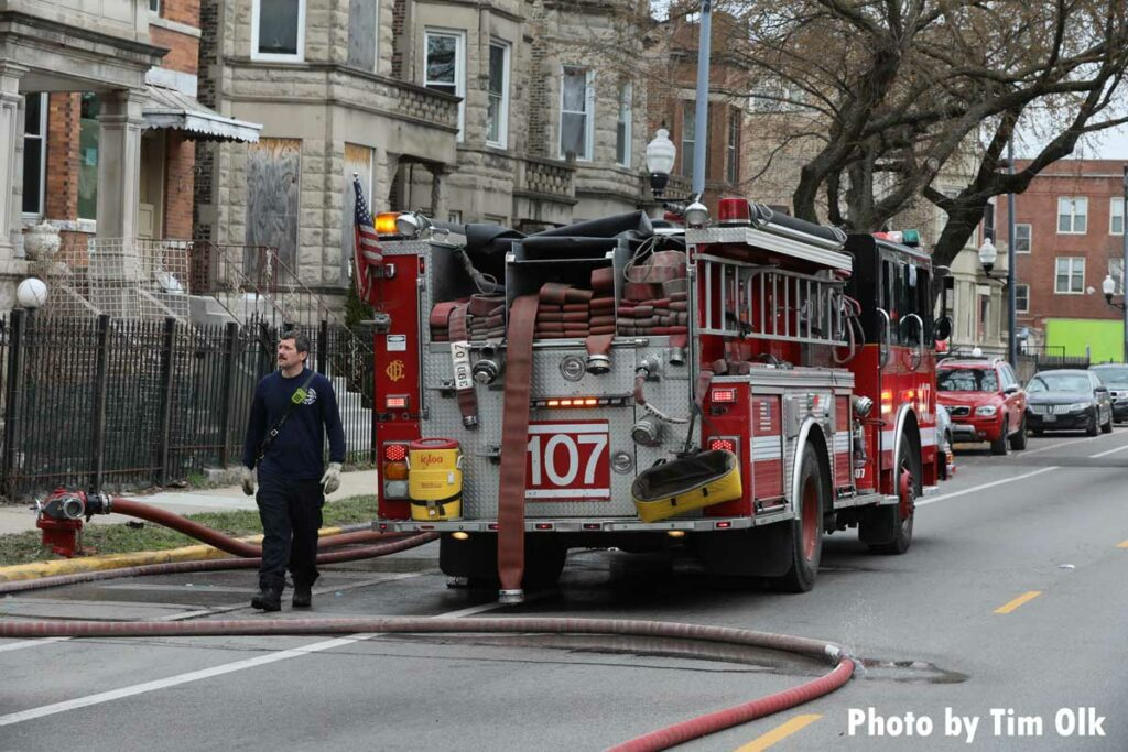 Firefighter with a section of LDH in front of a Chicago Fire Department fire apparatus