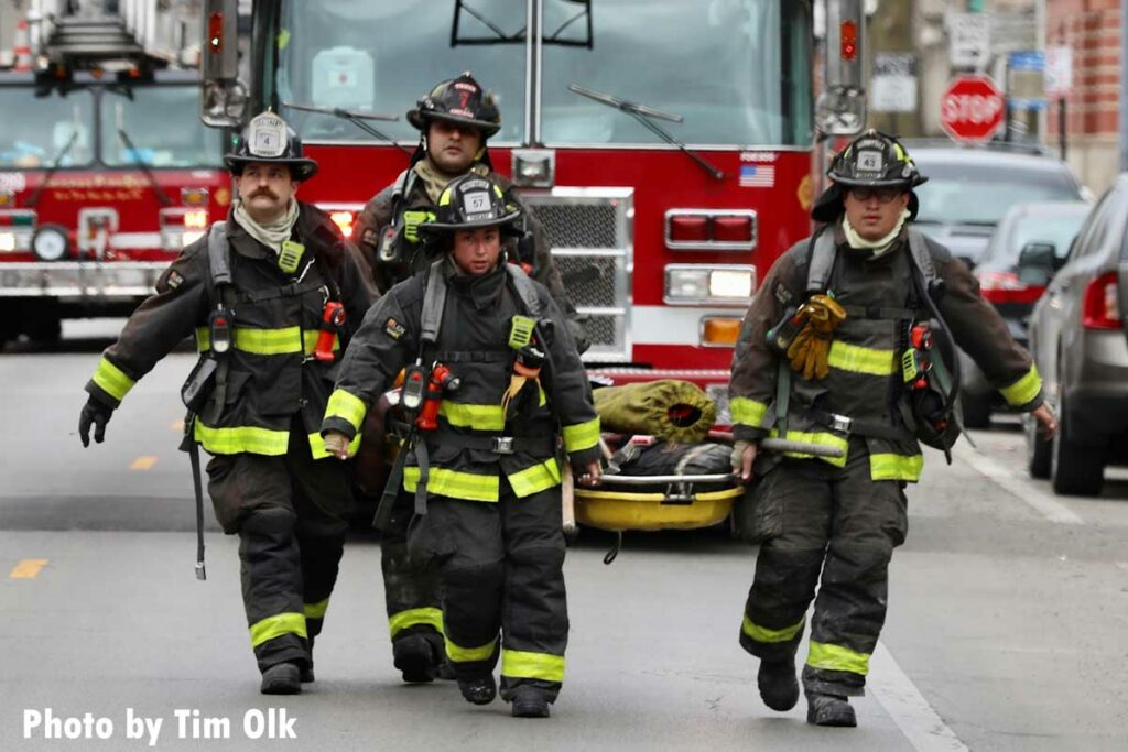 Four Chicago firefighters carry a stokes basket laden with gear from a rig