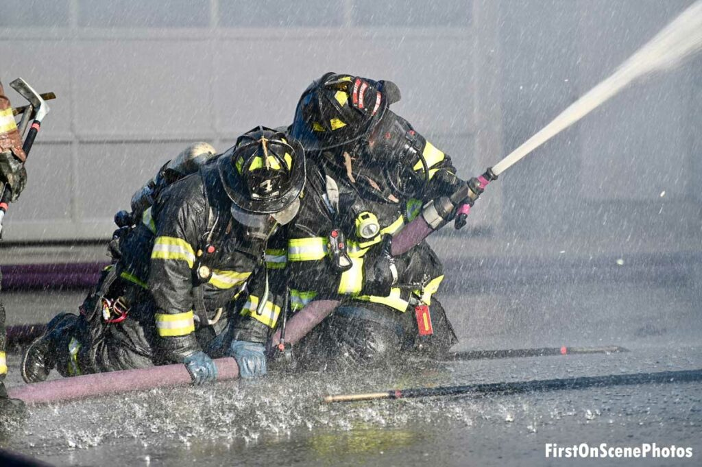 Multiple firefighters on a hoseline showered by water