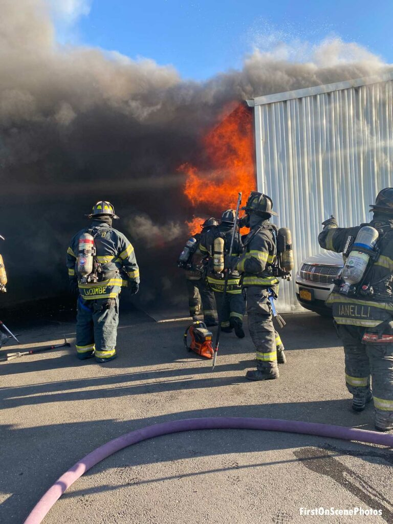 Fire shoots out from the side of the building as firefighters in full gear operate