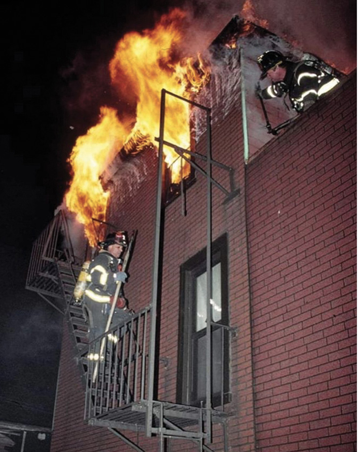 The roof firefighter recons the conditions in the rear while the outside vent firefighter operates from the fire escape below.