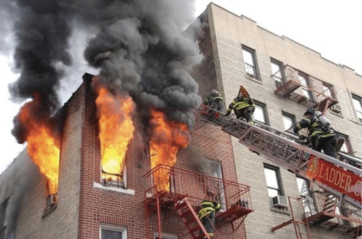 The outside vent firefighter patiently waits on the fire escape to vent the top-floor window as roof firefighters ascend the aerial directly above.