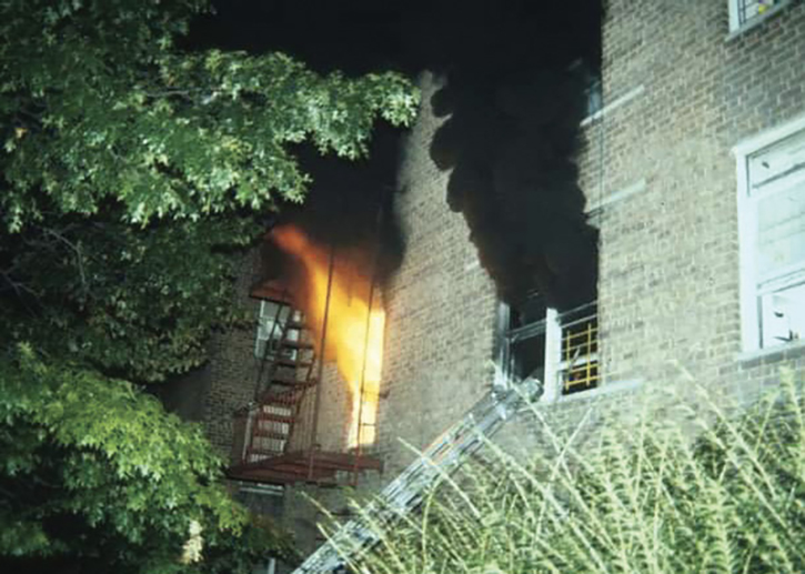 Heavy fire and thick, black smoke vent from the windows, indicating advanced and rapidly deteriorating conditions.