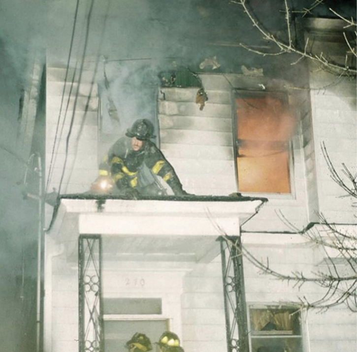 A rescue firefighter moves out onto the porch roof as conditions begin to deteriorate. topside.