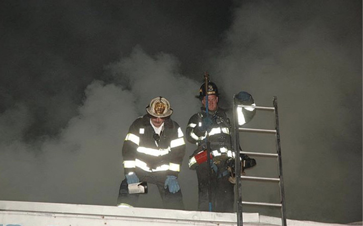 The battalion chief assigned to the roof division communicates with the incident commander on the conditions and progress of crews working topside.