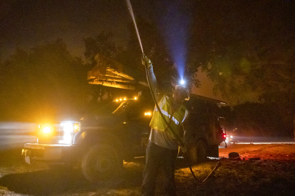 Worker sprays power lines during Zogg fire
