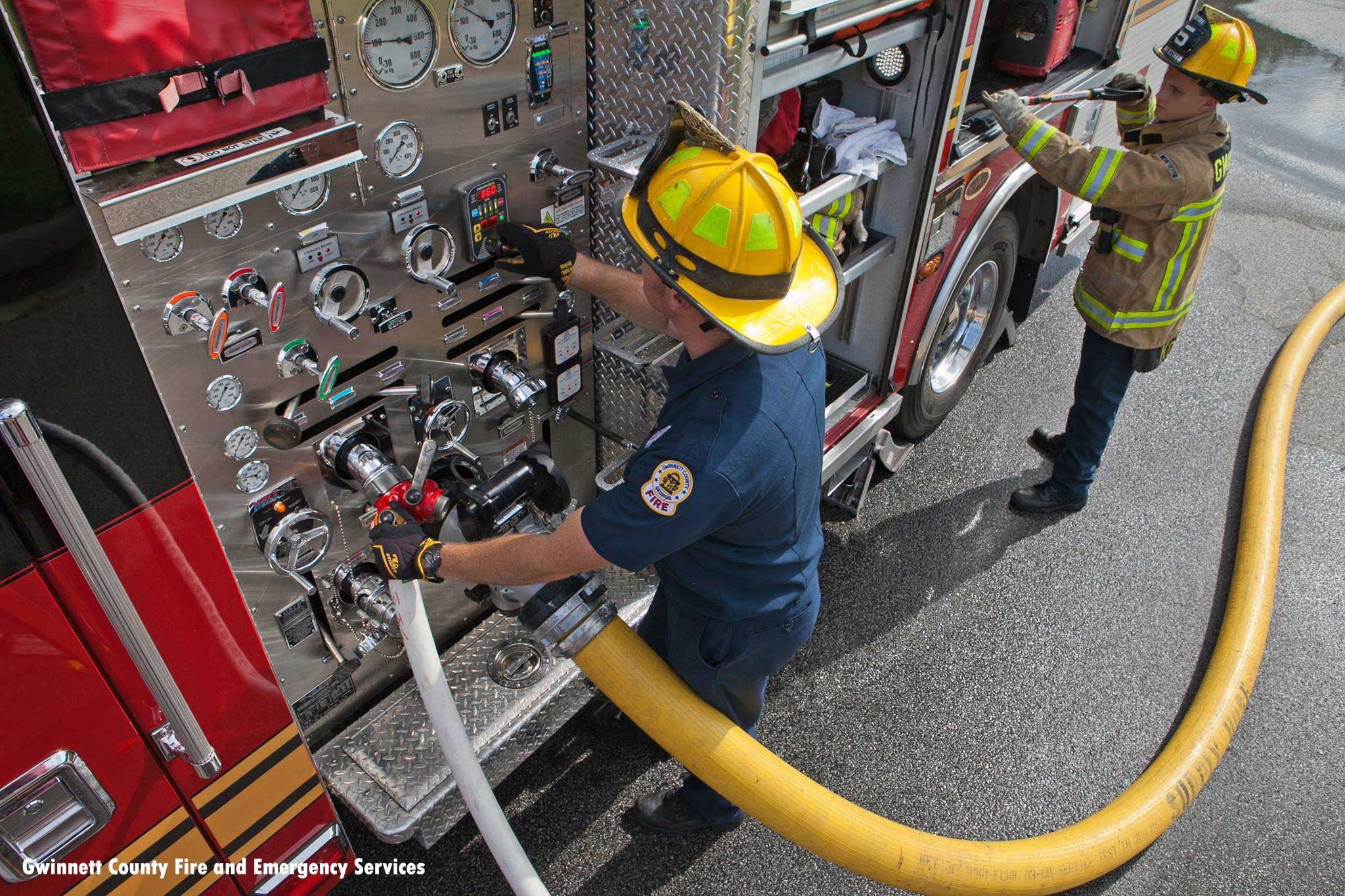 Firefighters work the pump panel