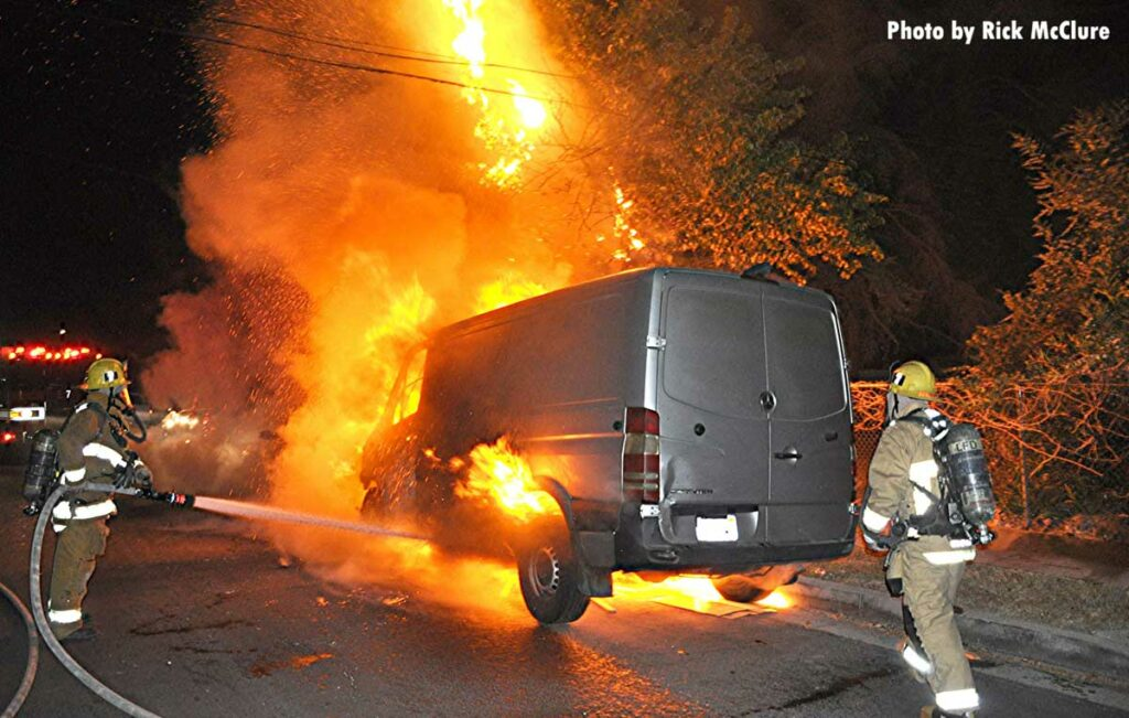 Two firefighters at a vehicle fire in Los Angeles
