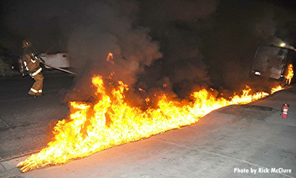 Flames race along flowing fuel from a vehicle fire