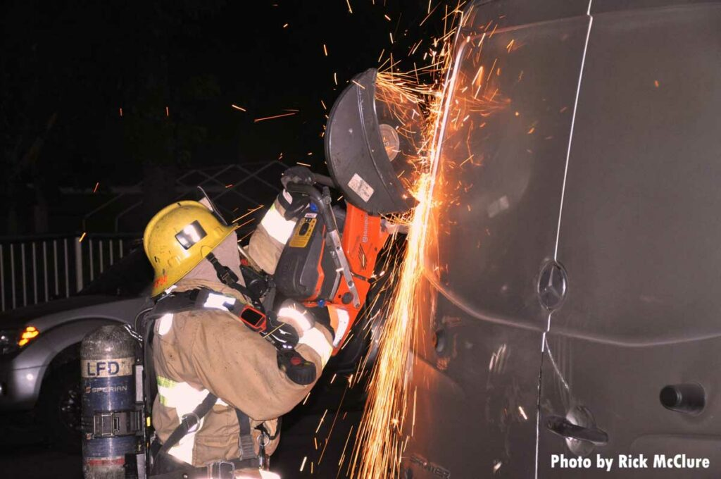 Firefighter using a circular saw to cut the rear door of a burning van