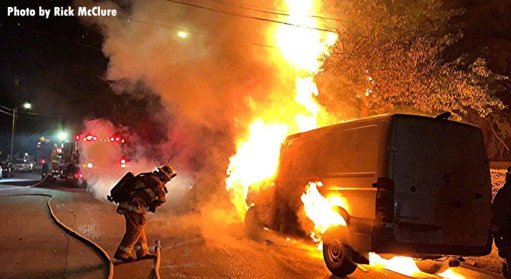 Firefighter puts water underneath a burning van