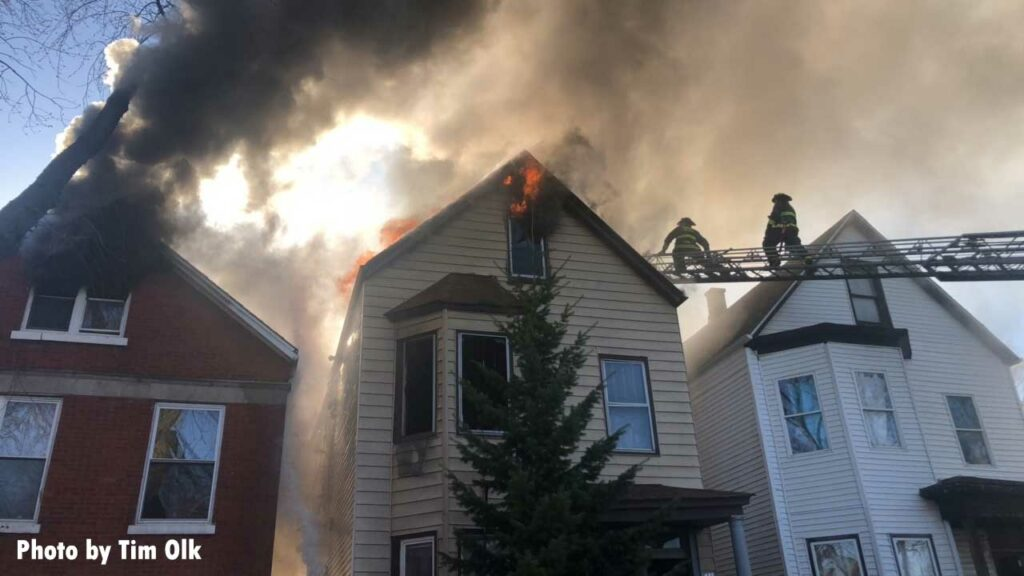 Smoke showing from one home with smoke and flame showing from another and Chicago firefighters on an aerial ladder
