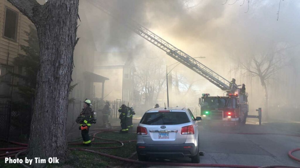 Chicago firefighters and an aerial ladder extended upward into smoke