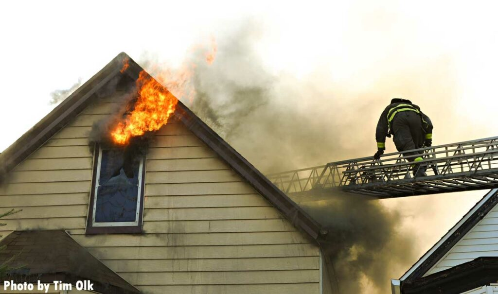 Flames shoot from above a window as a firefighter climbs a Chicago aerial ladder