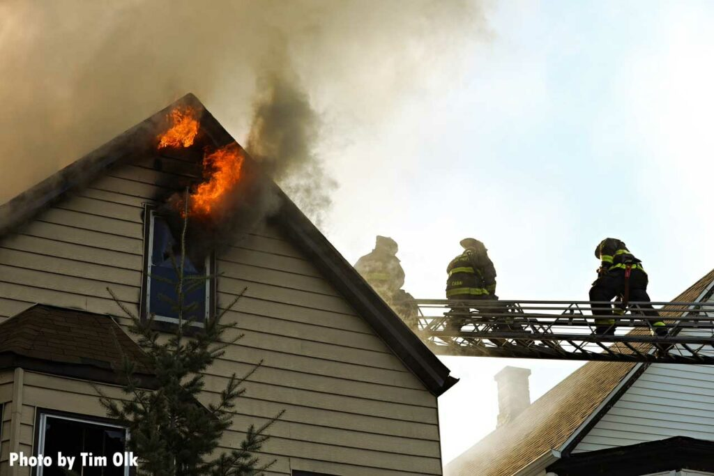 Flames shoot from the roofline as Chicago firefighter operate on aerial ladder