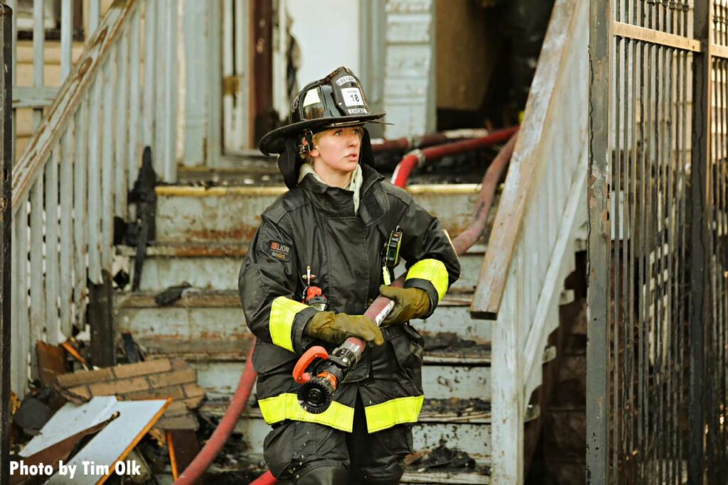 Chicago firefighter with hoseline in front of building
