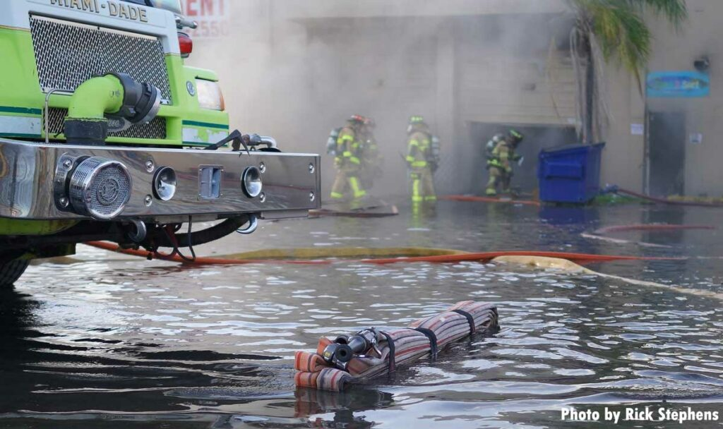 Miami-Dade fire apparatus with hose bundle in a pool of water