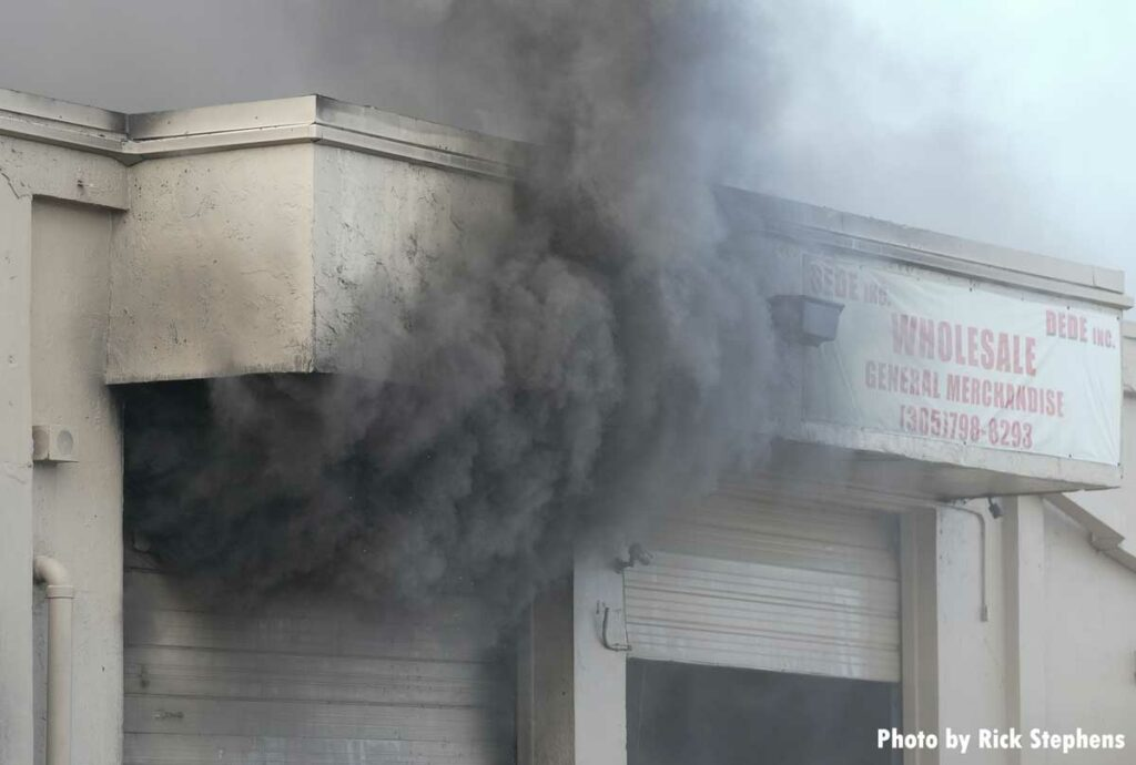 Smoke shoots out from a doorway at the warehouse