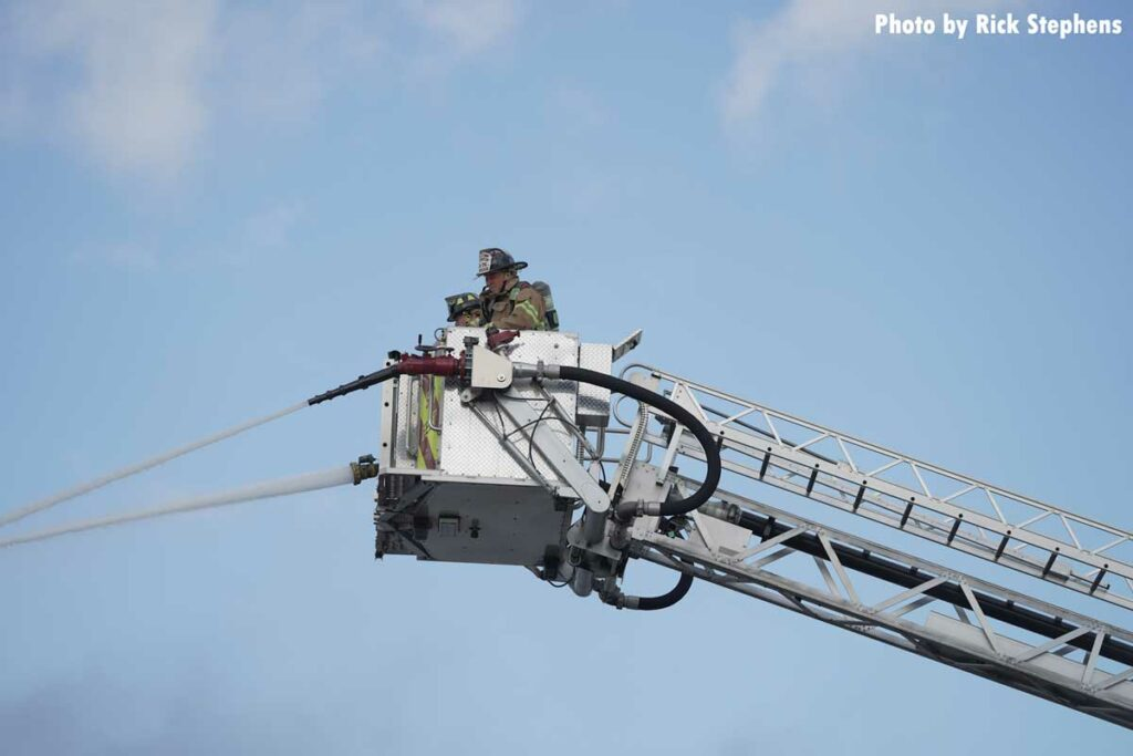 Firefighters in the tower ladder bucket with master streams