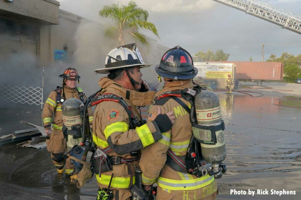 Firefighters at the warehouse fire near a pool of water