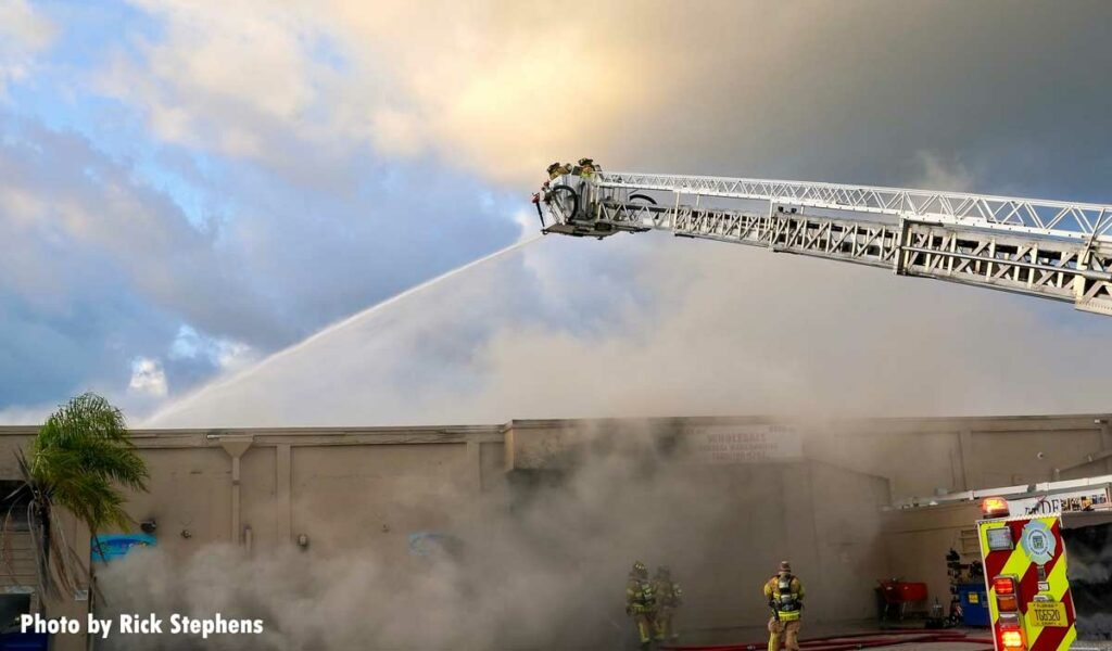 Firefighters in a tower ladder bucket with elevated master stream at warehouse fire
