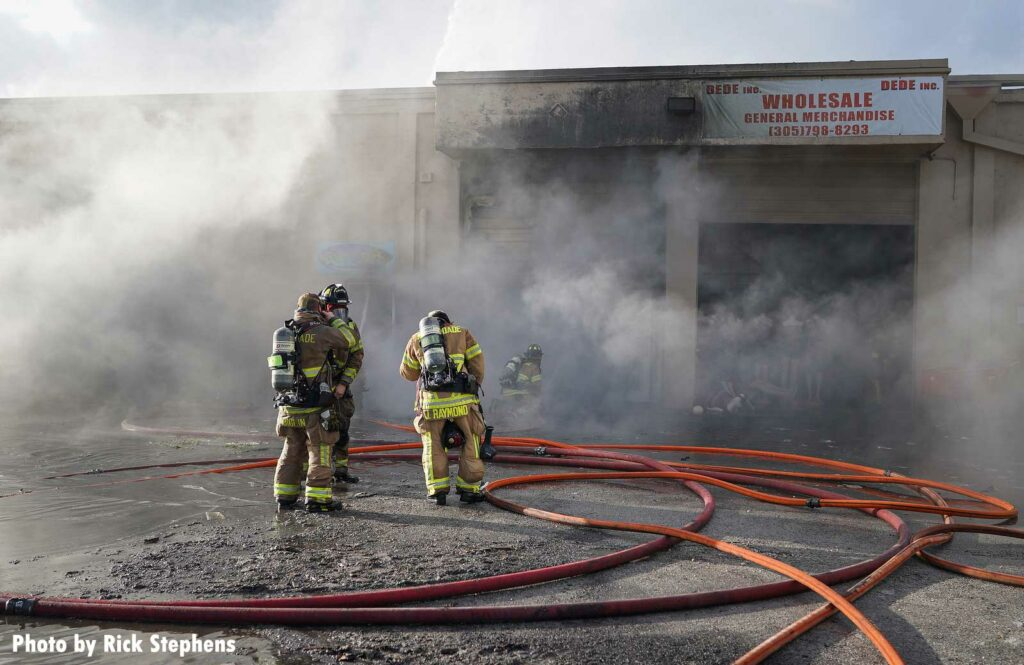 Firefighters and hoseline standing in the smoke at warehouse fire