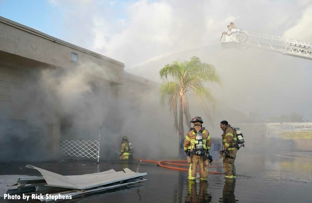 Firefighters in tower ladder put water on burning warehouse with other firefighter in foreground