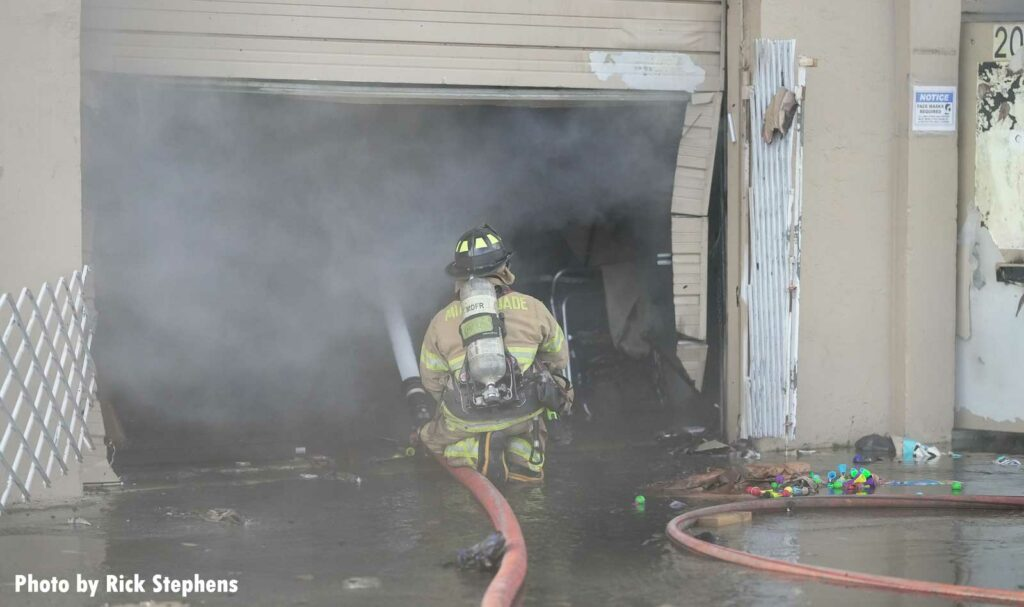 Firefighter puts a portable master stream inside the building