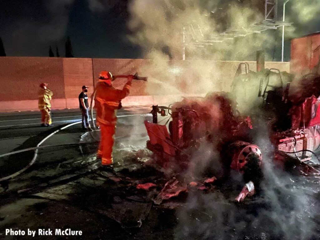 Firefighter pours water on burning tractor trailer on Los Angeles freeway