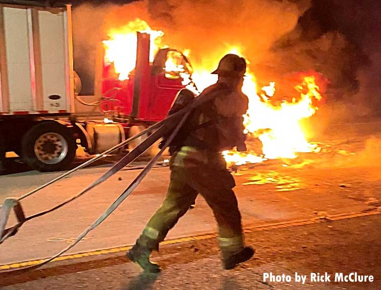 Firefighters flake out hoseline at semi fire