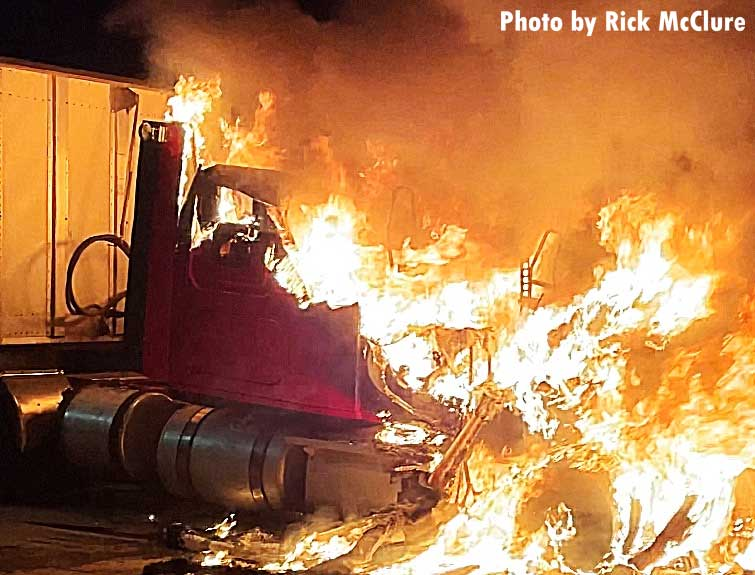 Close-up shot of flames tearing through cab of tractor trailer