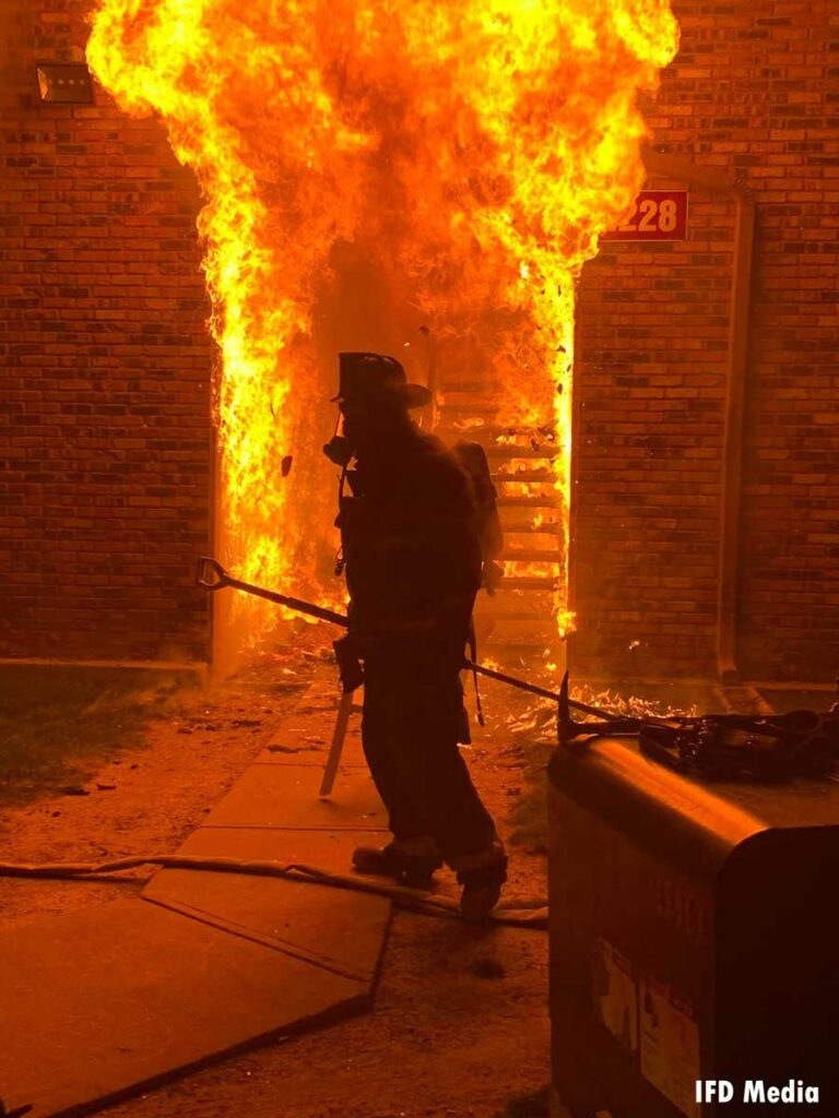 Flames roar from a doorway with an Indianapolis firefighter in front of it