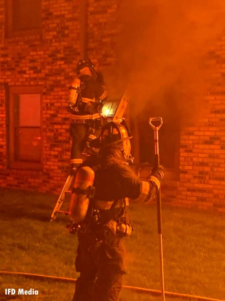 Firefighter ascends a ladder at the scene of a fire in Indianapolis while another firefighter is in the foreground with a hook