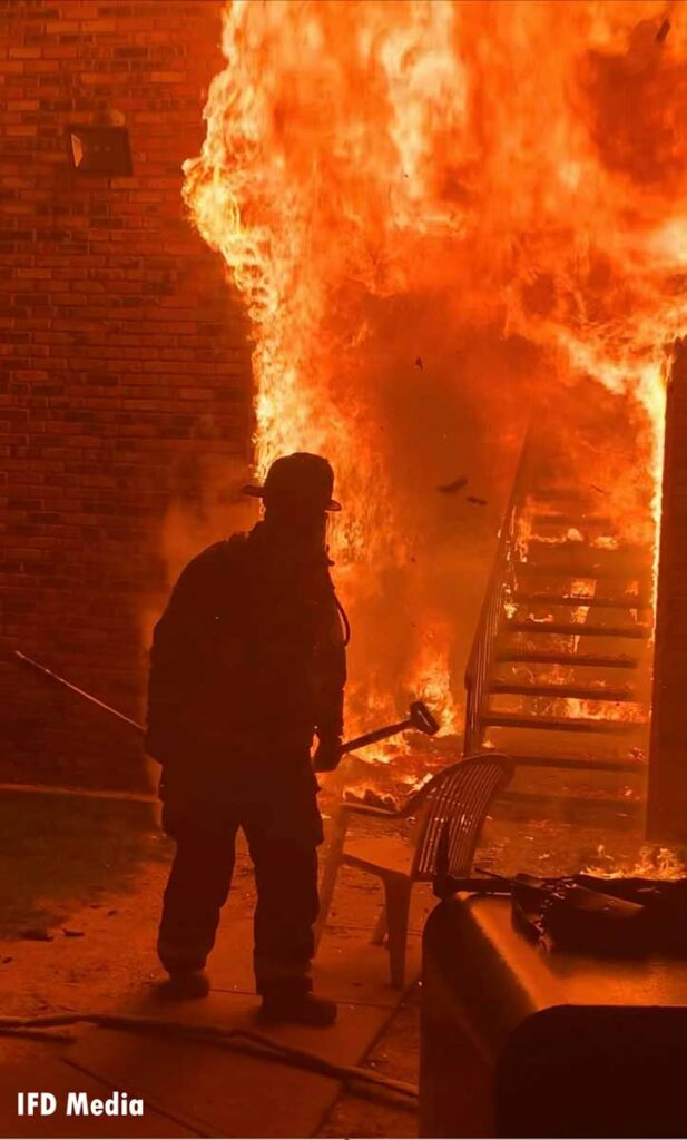 Firefighter with a hook with raging flames behind him