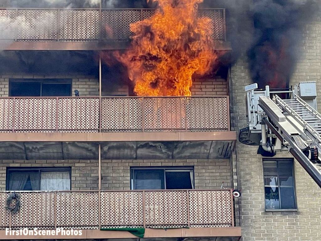 Firefighters at work at an apartment fire in Hempstead, New York, with flames ripping from balcony