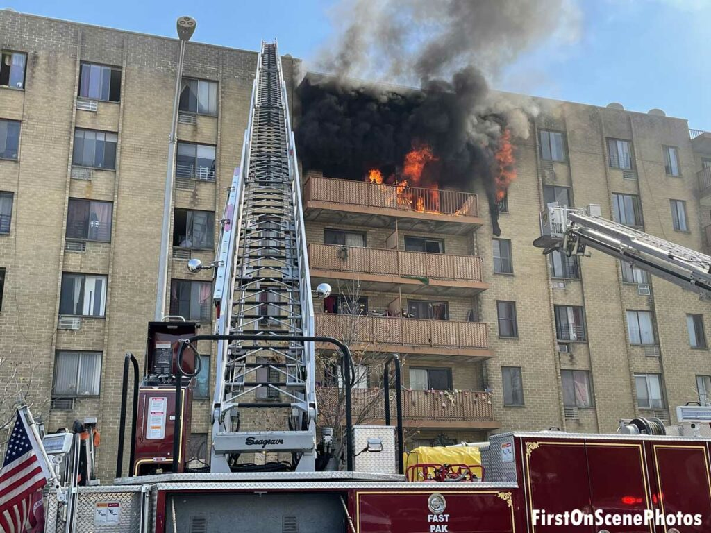 Flames and black smoke billow from the upper floor of an apartment with an aerial ladder reaching to the roof