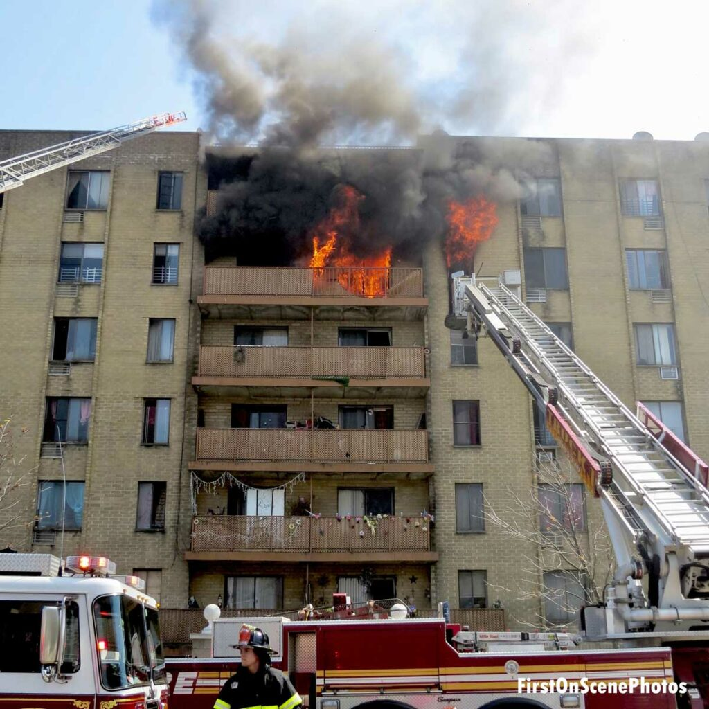 Fire burns on balcony at multi-story apartment in Hempstead with tower ladder and aerial ladder operating