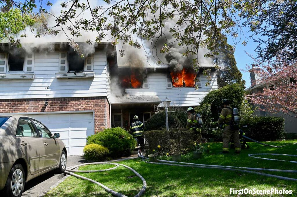Flames out two windows with hoselines in the yard in Searingtown, New York