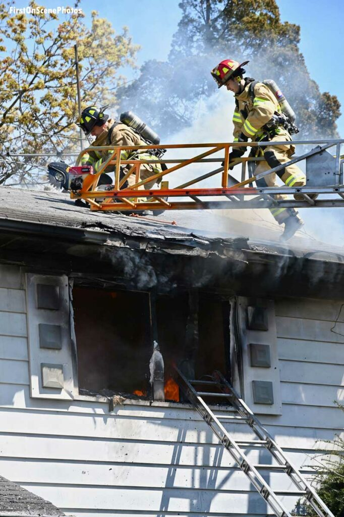 Firefighters make cuts from an aerial at a house fire