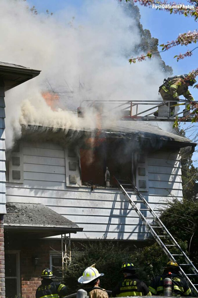 Smoke rolls up under the eaves as firefighters work on an aerial