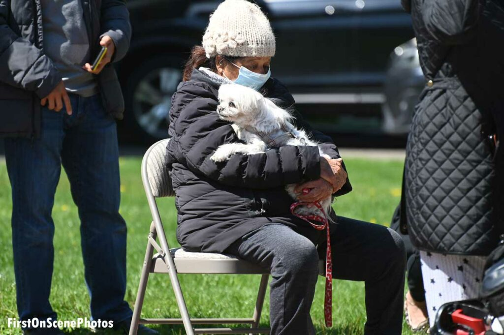 Person holding a dog at a house fire scene