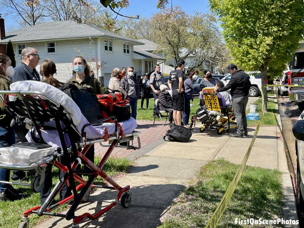 Firefighters and EMS providers with stretchers at house fire